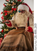 Santa Claus sitting in rocking chair near Christmas Tree at home and watching tv or home theater wearing 3d glasses and holding remote control. Стоковое фото, фотограф Kirill Kedrinskiy / Ingram Publishing / Фотобанк Лори