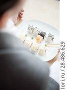 Купить «Young businesswoman eats sushi in formal dress», фото № 28486629, снято 11 января 2012 г. (c) Ingram Publishing / Фотобанк Лори