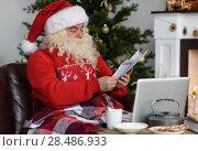 Купить «Santa Claus Working near Christmas Tree at Home. Reading childrens letters», фото № 28486933, снято 29 октября 2015 г. (c) Ingram Publishing / Фотобанк Лори