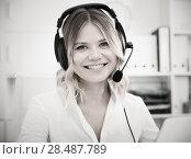 Купить «Young girl in call center with headphones sitting with laptop», фото № 28487789, снято 17 октября 2017 г. (c) Яков Филимонов / Фотобанк Лори