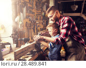 Купить «father and son with plane shaving wood at workshop», фото № 28489841, снято 14 мая 2016 г. (c) Syda Productions / Фотобанк Лори