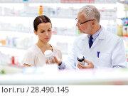 Купить «apothecary and woman with drug at pharmacy», фото № 28490145, снято 27 июня 2015 г. (c) Syda Productions / Фотобанк Лори