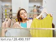 Купить «woman choosing clothes at clothing store», фото № 28490197, снято 19 февраля 2016 г. (c) Syda Productions / Фотобанк Лори