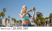 Купить «woman with smartphone and earphones doing sports», фото № 28490389, снято 5 июля 2015 г. (c) Syda Productions / Фотобанк Лори