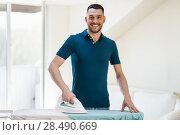 Купить «man ironing shirt by iron at home», фото № 28490669, снято 10 мая 2018 г. (c) Syda Productions / Фотобанк Лори