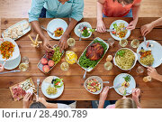 Купить «group of people eating at table with food», фото № 28490789, снято 5 октября 2017 г. (c) Syda Productions / Фотобанк Лори