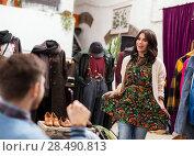 Купить «woman posing for boyfriend at clothing store», фото № 28490813, снято 30 ноября 2017 г. (c) Syda Productions / Фотобанк Лори