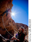 A female climber belays the leader during a rock climbing in Todra Valley, Atlas, Maroc, Africa. Стоковое фото, агентство Ingram Publishing / Фотобанк Лори