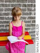 Купить «Girl draws on the album sitting bench 5055», фото № 28492329, снято 22 июля 2018 г. (c) Ingram Publishing / Фотобанк Лори