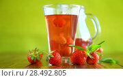 Купить «Sweet compote of ripe red strawberries in a glass decanter on a table», видеоролик № 28492805, снято 31 мая 2018 г. (c) Peredniankina / Фотобанк Лори