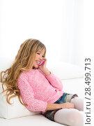 Купить «Blond kid girl playing fun talking to mobile smartphone on white sofa byod», фото № 28499713, снято 9 февраля 2014 г. (c) Ingram Publishing / Фотобанк Лори