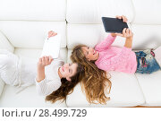 Купить «Children friends kid girls having fun playing with tablet pc lying on white sofa», фото № 28499729, снято 9 февраля 2014 г. (c) Ingram Publishing / Фотобанк Лори
