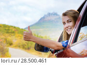 Купить «Happy driver woman shows thumb up against mountains background. Travel vacations concept», фото № 28500461, снято 26 сентября 2013 г. (c) Ingram Publishing / Фотобанк Лори