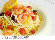 Seafood spaghetti pasta dish with shrimps cherry tomatoes and olives. Стоковое фото, агентство Ingram Publishing / Фотобанк Лори