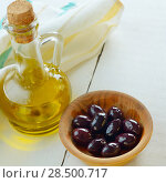 Купить «Olive oil and black olives on white table», фото № 28500717, снято 8 декабря 2019 г. (c) Ingram Publishing / Фотобанк Лори