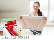 woman taking bath towels from drying rack at home. Стоковое фото, фотограф Syda Productions / Фотобанк Лори