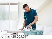 Купить «man ironing shirt by iron at home», фото № 28503597, снято 10 мая 2018 г. (c) Syda Productions / Фотобанк Лори