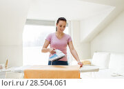 Купить «woman or housewife ironing towel by iron at home», фото № 28504061, снято 29 апреля 2018 г. (c) Syda Productions / Фотобанк Лори