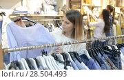 Купить «Portrait of smiling women choosing clothes in the modern shop», видеоролик № 28504493, снято 27 марта 2018 г. (c) Яков Филимонов / Фотобанк Лори