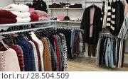 Купить «Ordinary apparel store with different clothes on hangers», видеоролик № 28504509, снято 26 апреля 2018 г. (c) Яков Филимонов / Фотобанк Лори