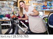 Купить «beautiful pregnant female looking for baby carriage at kids shop», фото № 28510765, снято 22 сентября 2017 г. (c) Яков Филимонов / Фотобанк Лори