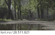 Купить «Child rides a bicycle over a puddle in summer day. Slow motion. Reflection», видеоролик № 28511821, снято 3 июня 2018 г. (c) Ирина Мойсеева / Фотобанк Лори