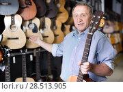 Купить «Smiling man musician buying new acoustic guitar», фото № 28513905, снято 18 сентября 2017 г. (c) Яков Филимонов / Фотобанк Лори