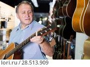 Купить «Man customer choosing new wooden acoustic guitar», фото № 28513909, снято 18 сентября 2017 г. (c) Яков Филимонов / Фотобанк Лори