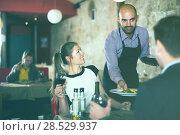 Купить «Waiter bringing salads to guests», фото № 28529937, снято 18 декабря 2017 г. (c) Яков Филимонов / Фотобанк Лори