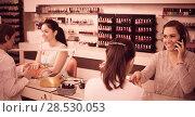 Купить «woman using smartphone during manicure at nail salon», фото № 28530053, снято 28 апреля 2017 г. (c) Яков Филимонов / Фотобанк Лори
