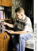 Купить «Мужчина выбирает книгу для чтения», фото № 28532069, снято 6 июня 2018 г. (c) Евгений Будюкин / Фотобанк Лори