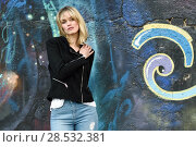 Купить «Attractive blonde woman in urban background. Young girl wearing black zipper jacket and blue jeans trousers standing in the street. Pretty female with straight hair hairstyle and blue eyes.», фото № 28532381, снято 22 января 2017 г. (c) Ingram Publishing / Фотобанк Лори