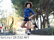 Купить «Young black woman with afro hairstyle jumping in urban background. Mixed woman wearing blue shirt and shorts. Female carrying funny headphones.», фото № 28532461, снято 10 декабря 2016 г. (c) Ingram Publishing / Фотобанк Лори