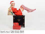 Купить «Beautiful happy blonde woman in Santa Claus clothes and striped socks moving her legs. Young funny girl with blue eyes carrying a sack of santa claus, isolated on white», фото № 28532581, снято 23 августа 2017 г. (c) Ingram Publishing / Фотобанк Лори