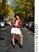 Купить «Young black woman with afro hairstyle standing in urban background», фото № 28532621, снято 10 декабря 2016 г. (c) Ingram Publishing / Фотобанк Лори
