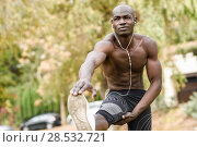 Fit shirtless young black man doing stretching before running in urban park. Young male exercising with naked torso listening to music with headphones. Стоковое фото, фотограф Javier Sánchez Mingorance / Ingram Publishing / Фотобанк Лори