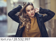 Купить «Blonde woman in urban background. Beautiful young girl wearing black leather jacket and mini skirt standing in the street. Pretty russian female with long wavy hair hairstyle and blue eyes.», фото № 28532997, снято 24 января 2017 г. (c) Ingram Publishing / Фотобанк Лори