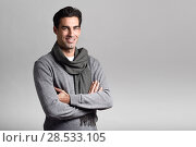 Купить «Handsome man wearing winter clothes smiling on white background. Young male with swater and scarf looking at camera. Studio shot», фото № 28533105, снято 17 ноября 2016 г. (c) Ingram Publishing / Фотобанк Лори