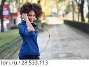 Купить «Young black woman with afro hairstyle listening to the music with headphones in urban background. Mixed funny woman wearing blue shirt and shorts.», фото № 28533113, снято 10 декабря 2016 г. (c) Ingram Publishing / Фотобанк Лори