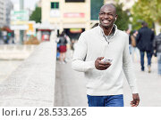 Купить «Black young man with a smartphone in his hand in urban background. Young african guy with shaved head wearing casual clothes and white headphones.», фото № 28533265, снято 20 ноября 2016 г. (c) Ingram Publishing / Фотобанк Лори