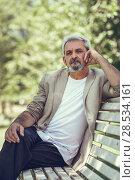 Купить «Pensive mature man sitting on bench in an urban park.», фото № 28534161, снято 9 июля 2017 г. (c) Ingram Publishing / Фотобанк Лори
