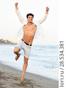 Купить «Portrait of an attractive young man jumping on a tropical beach. Handsome guy wearing white shirt and striped shorts. Male with beautiful body.», фото № 28534381, снято 7 июля 2016 г. (c) Ingram Publishing / Фотобанк Лори