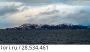 Sea with mountain in the background against cloudy sky, Norway. Стоковое фото, фотограф Keith Levit / Ingram Publishing / Фотобанк Лори