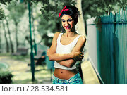 Купить «Portrait of a pin-up girl. American style, in a garden, wearing jeans and t-shirt», фото № 28534581, снято 20 мая 2012 г. (c) Ingram Publishing / Фотобанк Лори