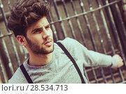 Купить «Portrait of young man wearing suspenders in urban background», фото № 28534713, снято 8 апреля 2014 г. (c) Ingram Publishing / Фотобанк Лори