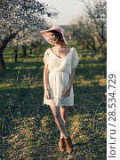 Купить «Portrait of young woman in the flowered field in the spring time. Almond flowers blossoms. Girl wearing white dress and pink sun hat», фото № 28534729, снято 10 марта 2015 г. (c) Ingram Publishing / Фотобанк Лори