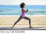 Купить «Black woman, afro hairstyle, doing yoga in warrior asana in the beach», фото № 28534805, снято 20 декабря 2017 г. (c) Ingram Publishing / Фотобанк Лори
