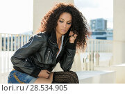 Купить «Black female, afro hairstyle, in urban background. Woman wearing denim shorts and leather jacket.», фото № 28534905, снято 11 декабря 2011 г. (c) Ingram Publishing / Фотобанк Лори