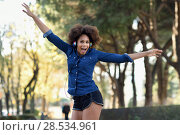 Купить «Young black woman with afro hairstyle jumping in urban background with open arms. Mixed woman wearing blue shirt and shorts. Female carrying funny headphones.», фото № 28534961, снято 10 декабря 2016 г. (c) Ingram Publishing / Фотобанк Лори