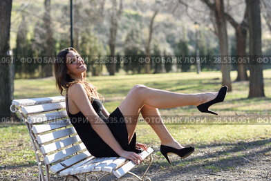 Portrait of funny woman, model of fashion with very long legs, sitting on a bench in an urban park, wearing black dress and high heels